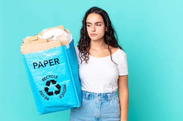 Spaanse mooie vrouw die zich verdrietig, overstuur of boos voelt en opzij kijkt en een gerecyclede papieren zak vasthoudt