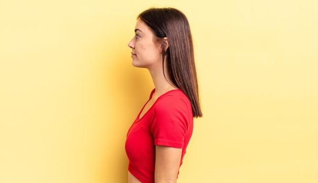 Spaanse mooie vrouw in profielweergave die ruimte vooruit wil kopiëren, denken, fantaseren of dagdromen