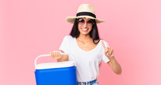 Spaanse mooie vrouw lacht en ziet er vriendelijk uit en toont nummer één met een draagbare picknickkoelkast