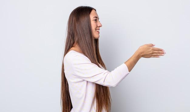 Spaanse mooie vrouw lacht, groet je en biedt een handdruk om een succesvolle deal te sluiten, samenwerkingsconcept