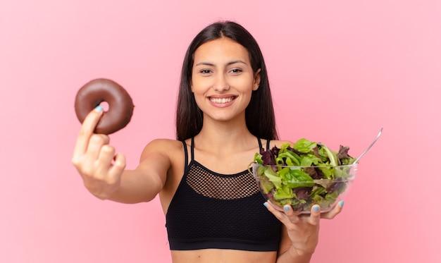 Spaanse mooie vrouw met een donut en een salade. dieet concept Premium Foto