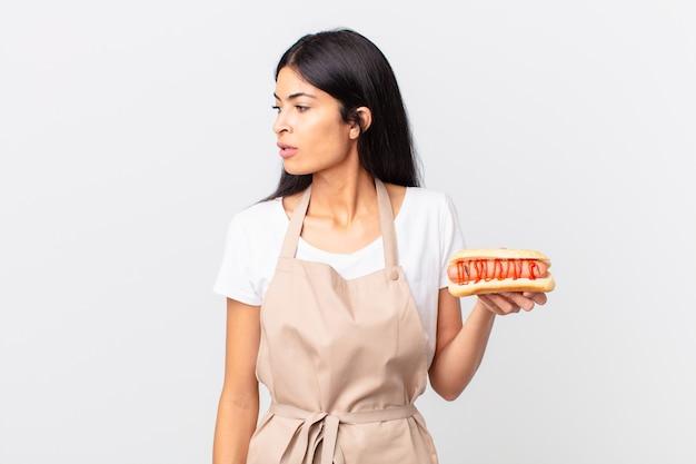 Spaanse mooie vrouw mooie spaanse chef-kok vrouw op profielweergave denken, verbeelden of dagdromen en een hotdog vasthouden