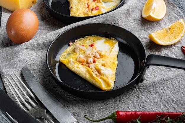 Spaanse omelet, verse rode chili, bruin en wit krabvlees, citroen, cheddarkaas, gebakken eieren, op koekenpan, op grijze achtergrond