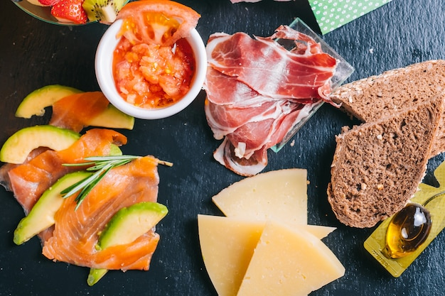 Spaanse ontbijtset met bezorgzalm en iberische ham, kaas, tomaten met sneetjes zwart brood in zwarte plaat