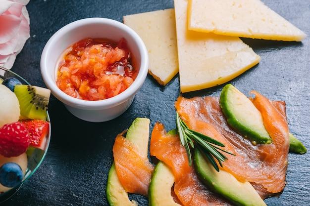 Spaanse ontbijtset met bezorgzalm en jamon, kaas, tomaten in zwarte plaat