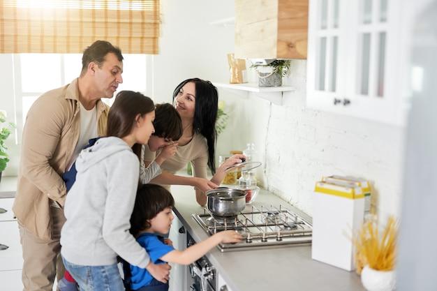 Spaanse ouders zien er gelukkig uit terwijl ze met kinderen in de keuken staan en samen thuis koken. gelukkige familie, kookconcept