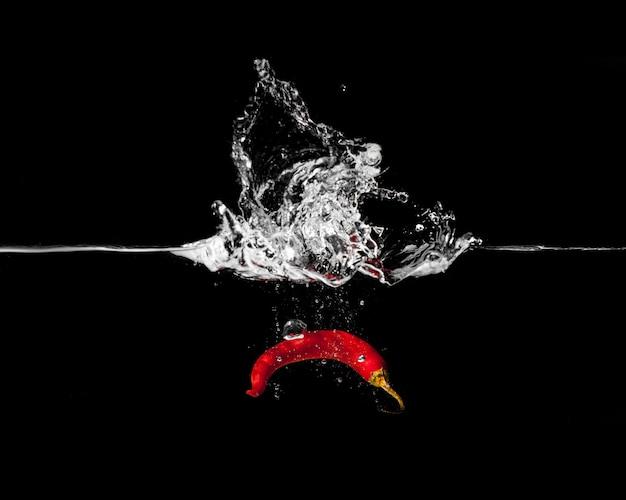 Spaanse pepergroenten die plons in water maken