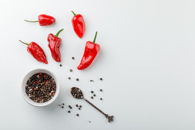 Spaanse pepers met peperbollen in lepel en plaat hoogste mening over een witte muur