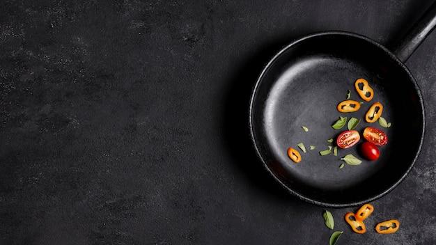 Spaanse peperspeper en tomaten in pan met exemplaar ruimteachtergrond