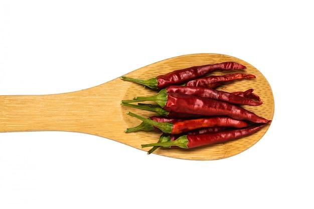 Spaanse peperspeulen in een houten lepel die op een witte achtergrond wordt geïsoleerd.