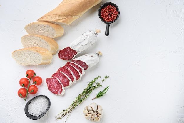 Spaanse salcichon plakjes met panini en kruiden op wit gestructureerd oppervlak met ruimte voor tekst.