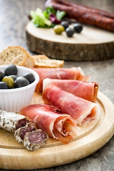 Spaanse serranoham, olijven en worstjes op hout