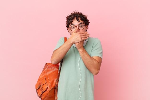 Spaanse student bedekt mond met handen met een geschokte, verbaasde uitdrukking, houdt een geheim of zegt oeps
