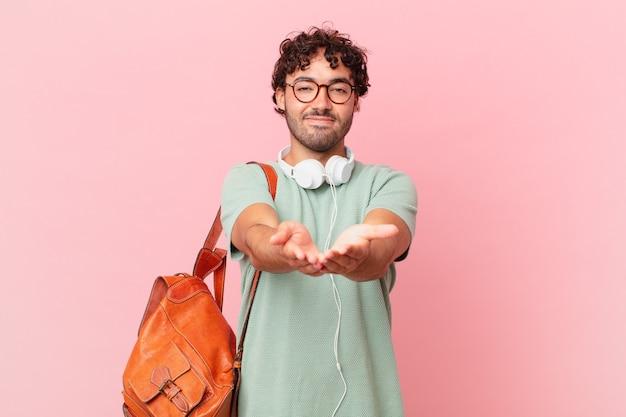 Spaanse student die gelukkig glimlacht met vriendelijke, zelfverzekerde, positieve blik, die een voorwerp of concept aanbiedt en toont