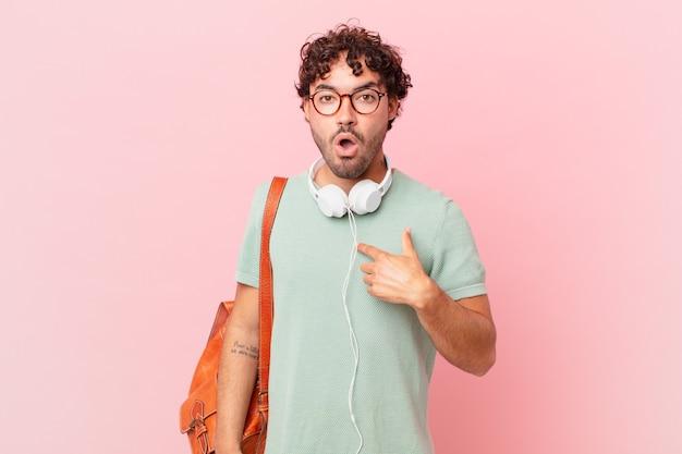Spaanse student kijkt geschokt en verrast met wijd open mond, wijzend naar zichzelf