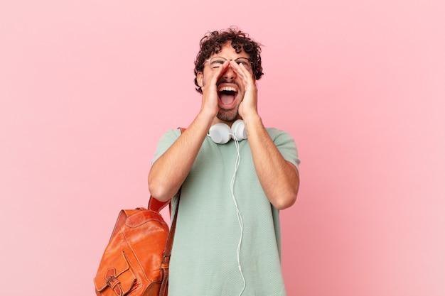 Spaanse student voelt zich blij, opgewonden en positief, geeft een grote schreeuw met handen naast de mond, roept