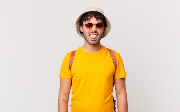 Spaanse toerist die walgt en geïrriteerd voelt, tong uitsteekt, niet van iets smerigs en vies houdt