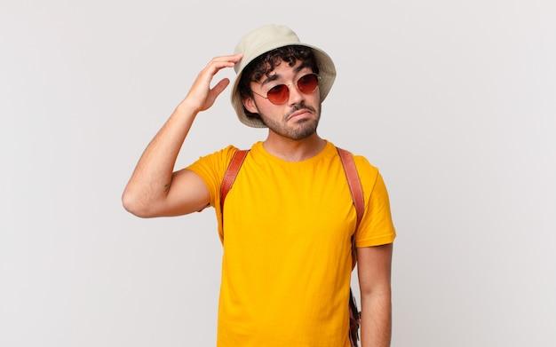 Spaanse toeristenmens die zich verbaasd en verward voelt, zijn hoofd krabt en naar de zijkant kijkt