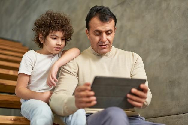 Spaanse vader van middelbare leeftijd zittend op de trap samen met zijn zoon schooljongen, met behulp van digitale tablet-pc tijdens het studeren op afstand thuis. quarantaine, thuisonderwijs, ouderschap