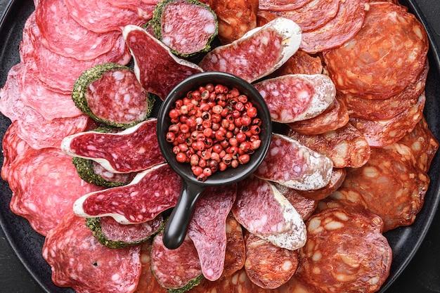 Spaanse vleeswaren plaat, chorizo, fuet, lomo, longaniza en salchichon op zwart, bovenaanzicht