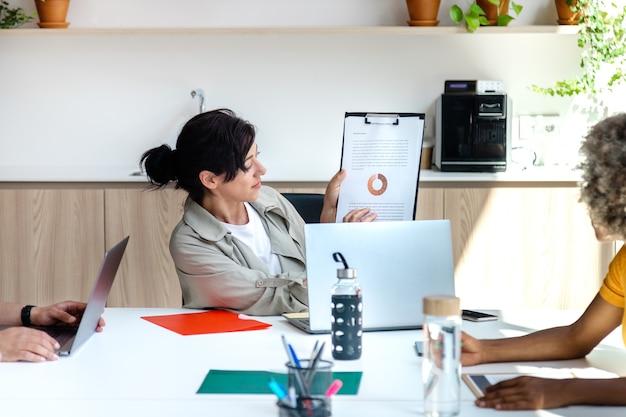 Spaanse vrouw baas toont werknemers grafiek van bedrijfsresultaten zakelijke bijeenkomst vrouwelijke baas concept