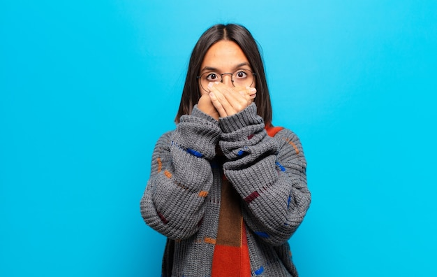 Spaanse vrouw bedekt mond met handen met een geschokte, verbaasde uitdrukking, houdt een geheim of zegt oeps