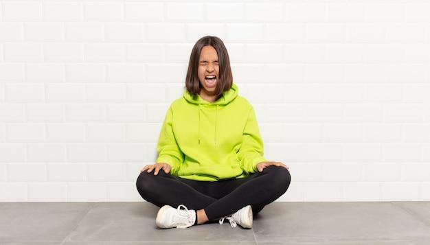 Spaanse vrouw die agressief schreeuwt, er erg boos, gefrustreerd, verontwaardigd of geïrriteerd uitziet, nee schreeuwt