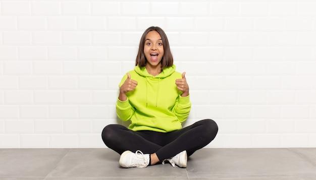 Spaanse vrouw die breed kijkt gelukkig, positief, zelfverzekerd en succesvol, met beide duimen omhoog