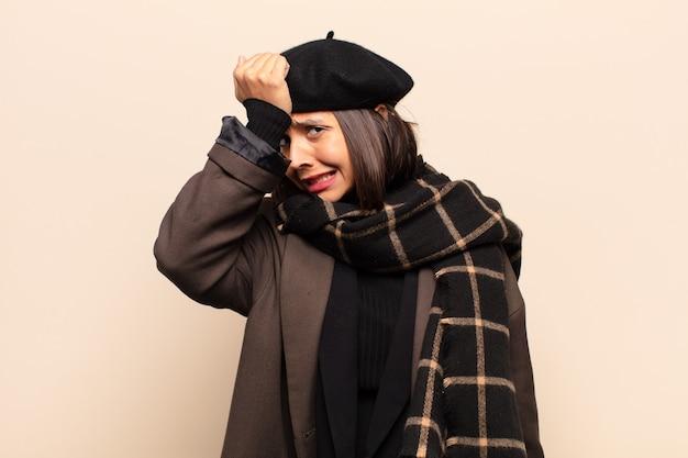 Spaanse vrouw die de handpalm naar het voorhoofd opheft, denkend oeps, na het maken van een domme fout of het zich herinneren, zich dom voelen