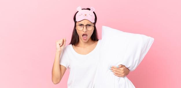 Spaanse vrouw die een pyjama draagt die agressief schreeuwt met een boze uitdrukking en een kussen vasthoudt