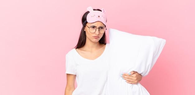Spaanse vrouw die een pyjama draagt die zich verdrietig, overstuur of boos voelt en opzij kijkt en een kussen vasthoudt