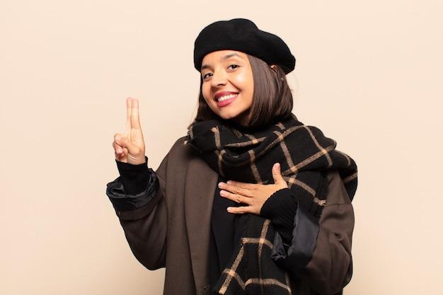 Spaanse vrouw die er gelukkig, zelfverzekerd en betrouwbaar uitziet, glimlacht en een overwinningsteken toont, met een positieve houding