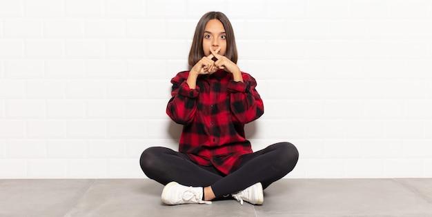 Spaanse vrouw die er serieus en ontevreden uitziet met beide vingers vooraan gekruist in afwijzing, en vraagt om stilte