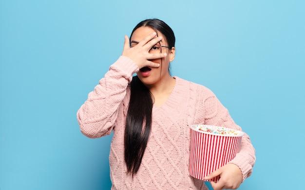 Spaanse vrouw die geschokt, bang of doodsbang kijkt, gezicht bedekt met hand en tussen vingers gluurt