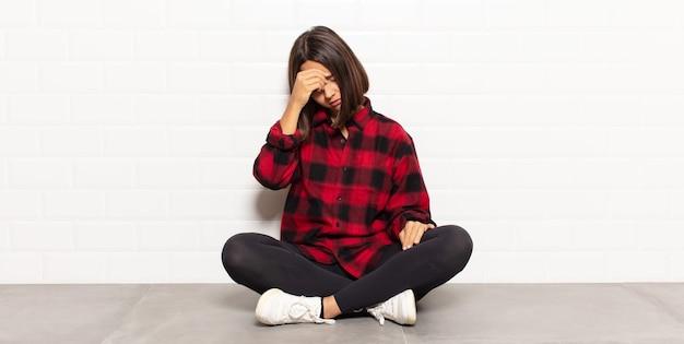 Spaanse vrouw die gestrest, beschaamd of boos kijkt, met hoofdpijn, gezicht bedekt met hand