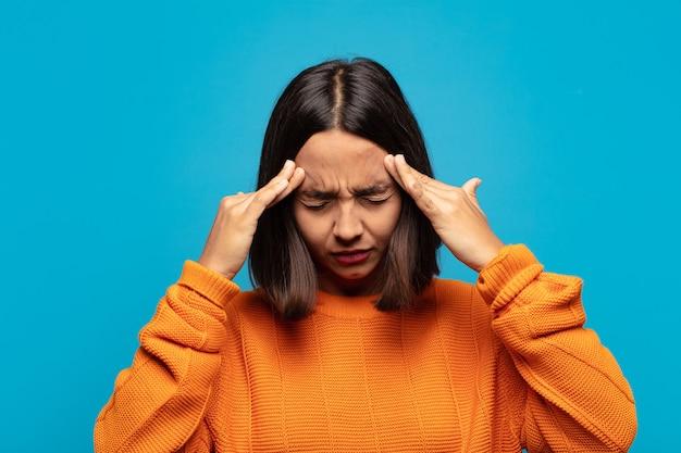 Spaanse vrouw die gestrest en gefrustreerd kijkt, onder druk werkt met hoofdpijn en last heeft van problemen