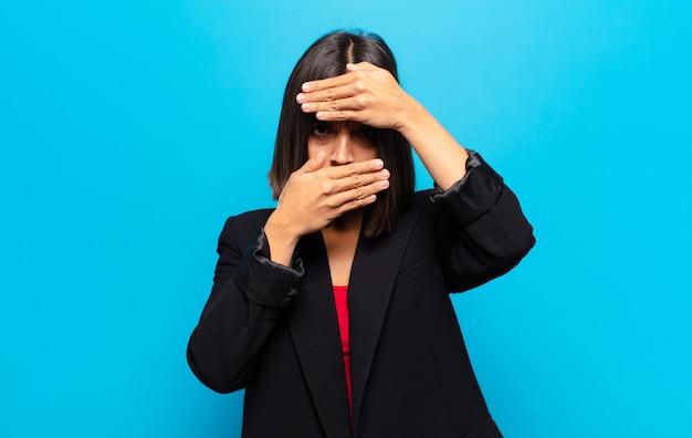 Spaanse vrouw die gezicht bedekt met beide handen en zegt nee tegen de camera! afbeeldingen weigeren of foto's verbieden