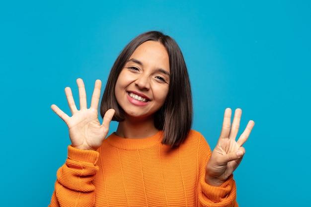 Spaanse vrouw die lacht en er vriendelijk uitziet, nummer acht of achtste toont met de hand naar voren, aftellend