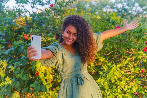 Spaanse vrouw die lacht terwijl ze een arm opheft en een selfie maakt met een smartphone
