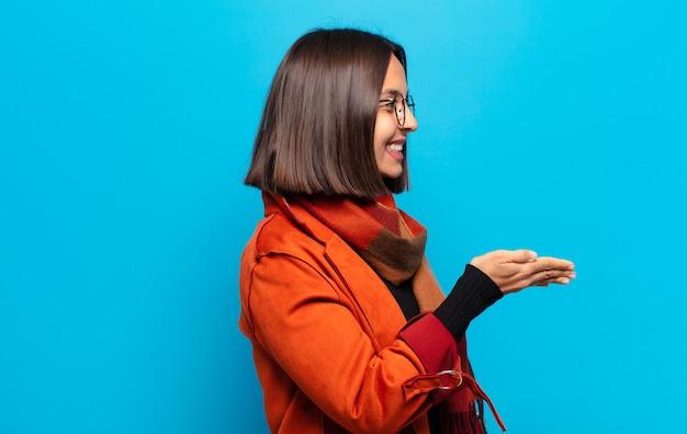 Spaanse vrouw die lacht, u begroet en een handschud aanbiedt om een succesvolle deal, samenwerkingsconcept te sluiten