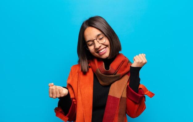 Spaanse vrouw die lacht, zich onbezorgd, ontspannen en gelukkig voelt, danst en naar muziek luistert, plezier heeft op een feestje