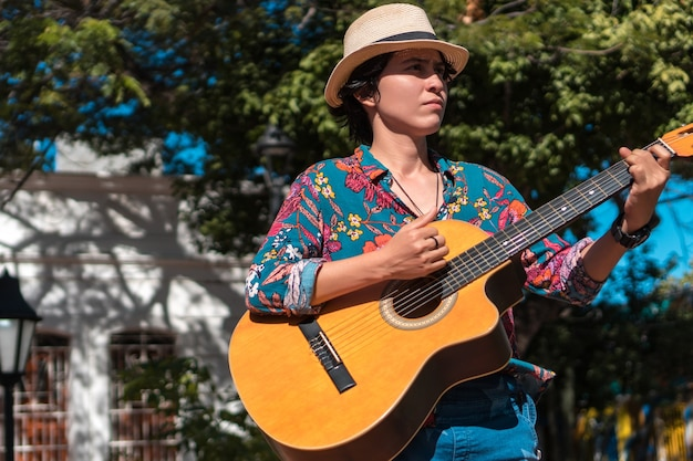Spaanse vrouw die met gitaarkoffer omhoog kijkt