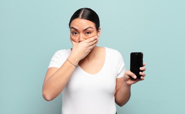 Spaanse vrouw die mond bedekt met handen met een geschokte, verbaasde uitdrukking, een geheim bewaren of oeps zeggen