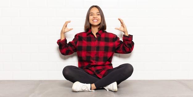 Spaanse vrouw die of eigen glimlach met beide handen omlijst of schetst, die positief en gelukkig kijkt, wellnessconcept