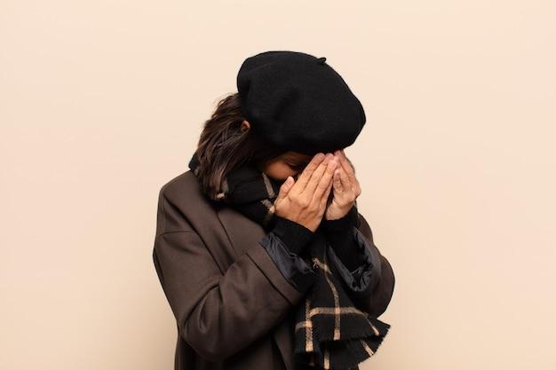 Spaanse vrouw die ogen bedekt met handen met een droevige, gefrustreerde blik van wanhoop, huilend, zijaanzicht