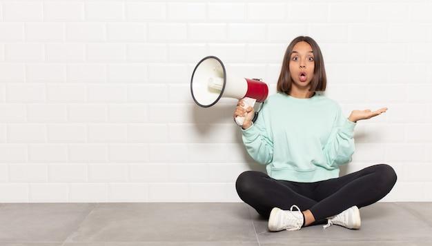 Spaanse vrouw die verbaasd en geschokt kijkt, met open mond een voorwerp vasthoudt met een open hand op de zijkant