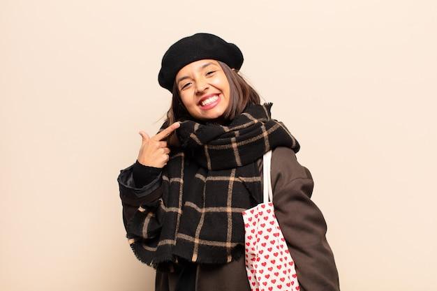 Spaanse vrouw die vol vertrouwen glimlacht en wijst naar een brede glimlach, een positieve, ontspannen, tevreden houding