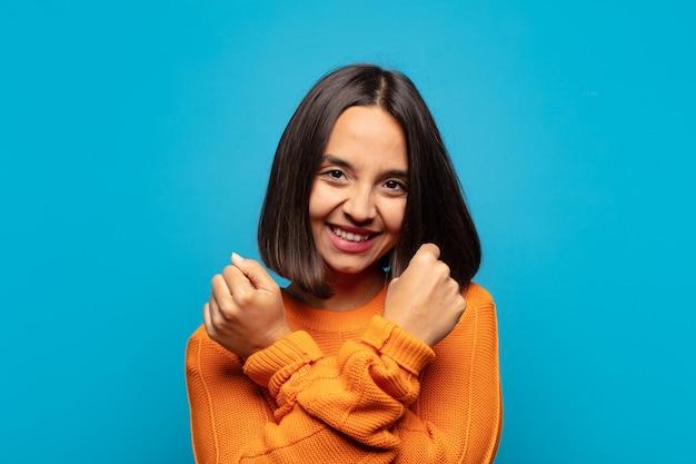 Spaanse vrouw die vrolijk glimlacht en viert, met gebalde vuisten en gekruiste wapens, zich gelukkig en positief voelt