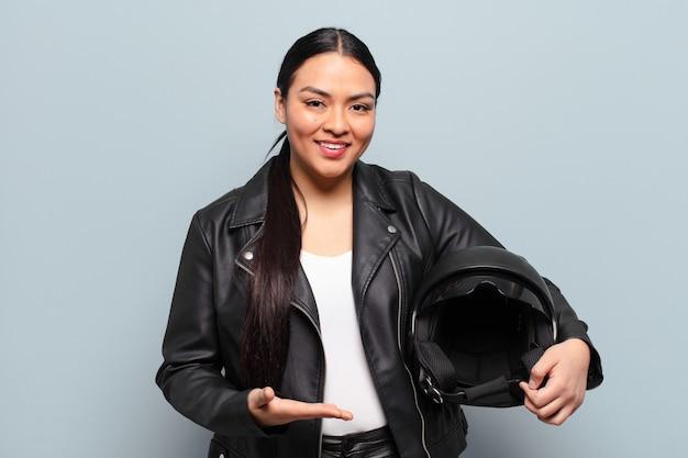 Spaanse vrouw die vrolijk glimlacht, zich gelukkig voelt en een concept in exemplaarruimte met handpalm toont