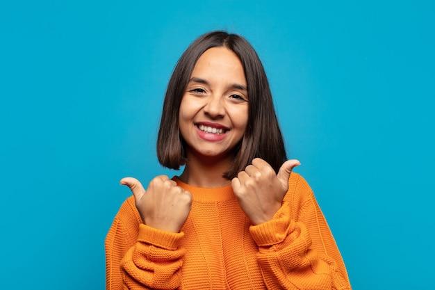 Spaanse vrouw die vrolijk lacht en er gelukkig uitziet, zich zorgeloos en positief voelt met beide duimen omhoog